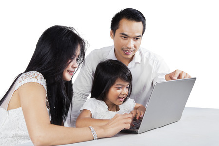 Two asian parents using laptop computer with their daughter on the table photo