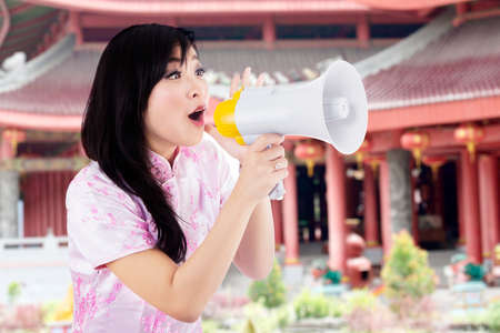 yelling: Happy young woman yelling with megaphone