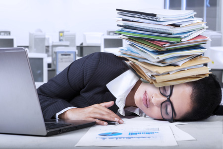 Female entrepreneur with tired expression sleeping in the office with paperwork on her head photo