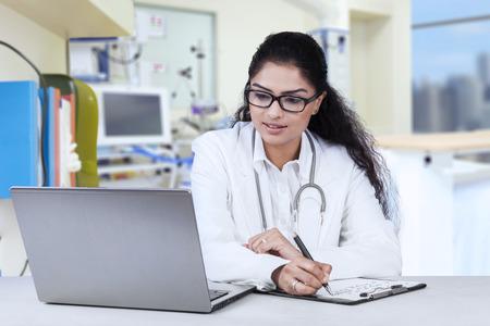 estudiando: Retrato del doctor joven que trabaja en el hospital mientras mira la computadora portátil y escribir en el portapapeles
