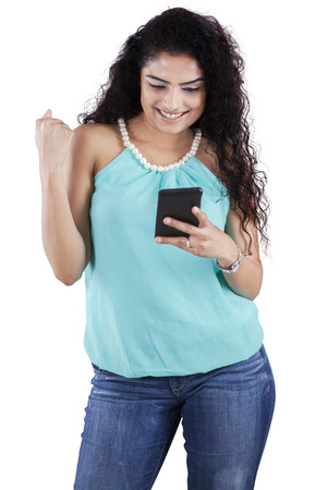 messaging: Portrait of cheerful girl with long curly hair reading message on the mobile phone