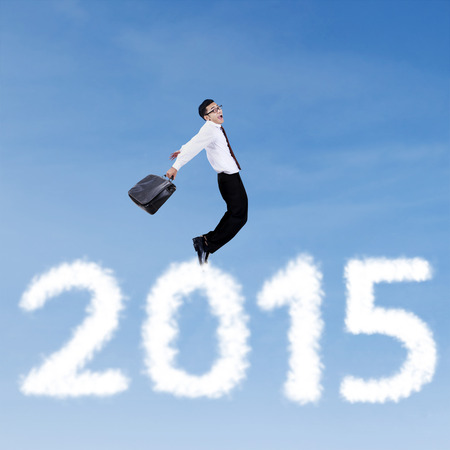 Businessman holding briefcase flying on the sky above cloud shaped number 2015 photo