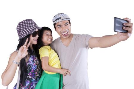 při pohledu na fotoaparát: Asijské rodina používat telefon s fotoaparátem, aby autoportrét společně ve studiu Reklamní fotografie