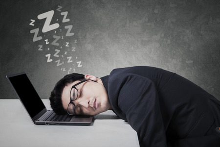 tired businessman: Portrait of caucasian businessperson with glasses, sleeping on the laptop computer Stock Photo