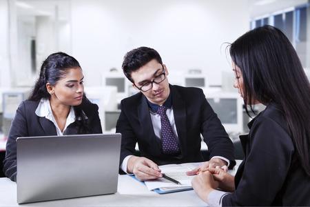 contratos: Hombre de negocios joven con su ayudante mostrando y explicando un documento de negocios a su pareja