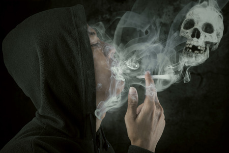 inhale: Young man wearing jacket smoking over a black background, shot in the studio
