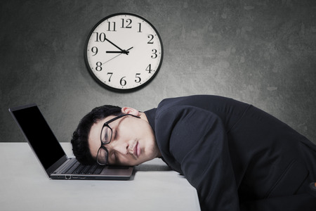 Tired caucasian businessman in business suit work overtime and sleep on laptop