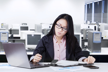 finance manager: Young chinese businesswoman working in the office while making a plan on notebook Stock Photo