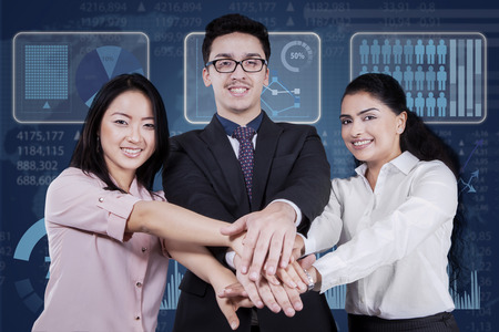 joining hands: Portrait of young multicultural businesspeople smiling at the camera while joining hands