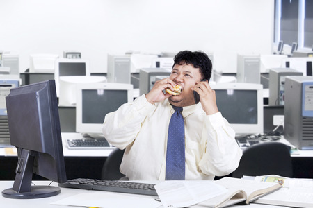 fat man: Overweight businessman working in the office while eating burger and calling with mobilephone Stock Photo