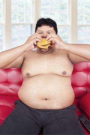 persona seduta: Ritratto di persona in sovrappeso, seduto sul divano mentre mangia hamburger Archivio Fotografico
