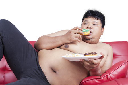 fat people: Lazy fat person eating donuts while sitting on the sofa, isolated on white background Stock Photo
