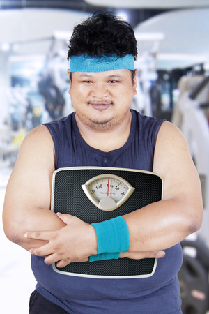 sports wear: Overweight person in sports wear holding a scale in the fitness center