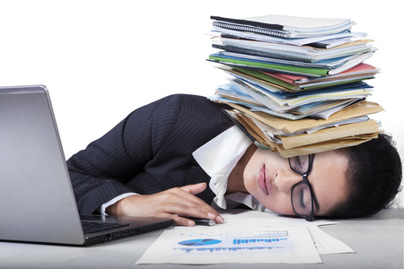 Tired female entrepreneur sleeping on desk with paperwork on her head photo