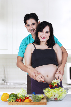 Portrait of two young parents with pregnant belly cooking vegetables salad in the kitchen photo