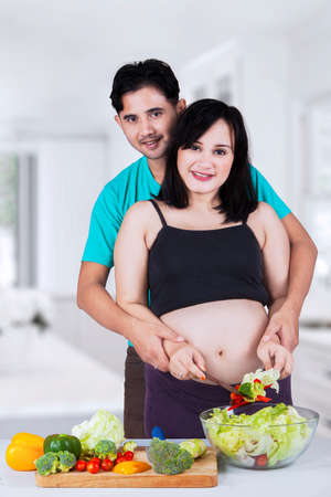Young pregnant woman with her husband making vegetables salad in the kitchen photo