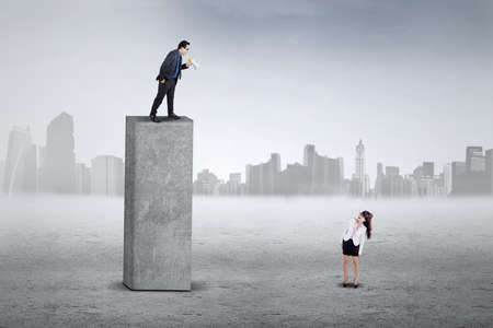 arrogancia: Joven empresaria tiene miedo después de ver en su jefe en la parte superior con un megáfono Foto de archivo