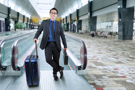 Portrait of male entrepreneur in business suit smiling at the camera while carrying luggage and briefcase in the airport hall photo