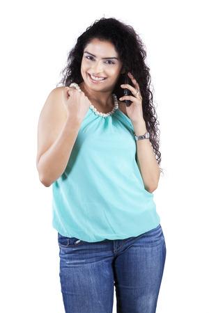 llamando: Retrato de la muchacha ocasional joven con el pelo rizado expresando el éxito mientras se habla por el teléfono