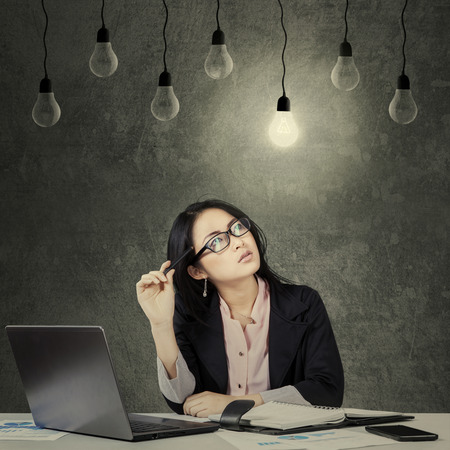Portrait of young female entrepreneur thinking while looking up at lightbulb photo