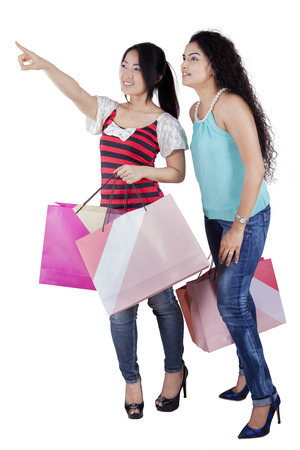 spending full: Happy girls carrying shopping bags and looking at copyspace, isolated on white background Stock Photo