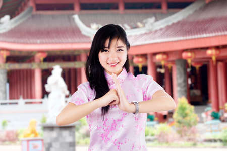 chinese dress: Beautiful young asian woman with gesture of congratulation
