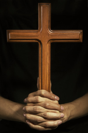 Person holding a wooden cross, symbolizing religious man photo