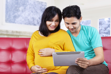 Portrait of asian man sitting on sofa while using a digital tablet with his pregnant wife photo