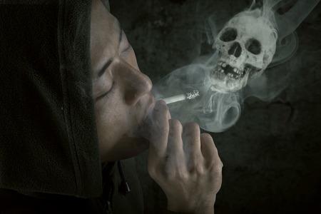 Person enjoying cigarette with smoke shaped skull, shot over black background photo