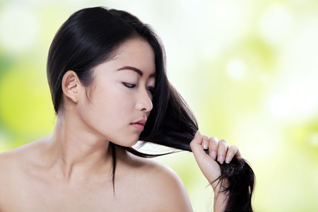 hair studio: Attractive woman with long black hair looking at her hair against defocused light background