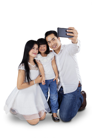 Portrait of cheerful family using mobile phone to take self photo in the studio