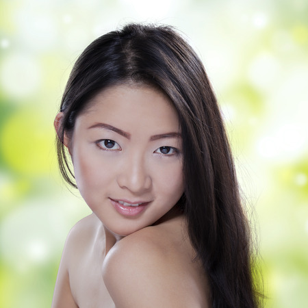 Portrait of a young asian woman with healthy skin after spa smiling at the camera against bokeh background photo