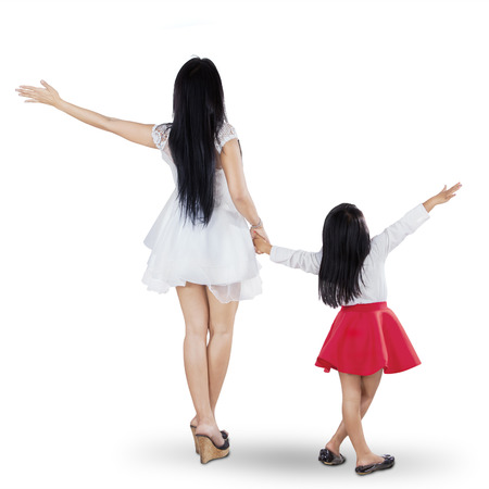 Rear view of young mother and daughter holding hands in the studio Фото со стока