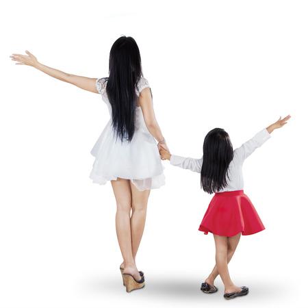 Vista posterior de la madre y la hija holding joven manos en el estudio