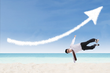 upturn: Happy businessman perform success move at beach under up arrow sign Stock Photo