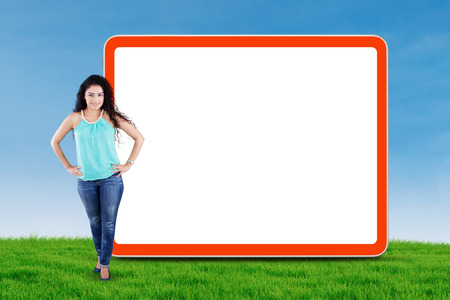 indian student: Full length of young asian woman with casual clothes, standing next to empty billboard at field Stock Photo
