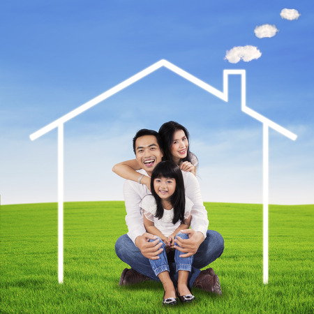 Portrait of happy family sitting on the meadow with green grass under a dream house