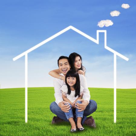 ni�as chinas: Retrato de familia feliz sentado en el prado con hierba verde bajo una casa de ensue�o