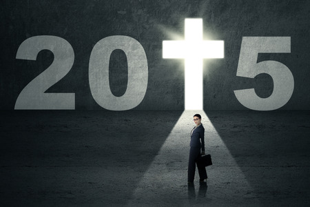 carrying the cross: Businesswoman carrying briefcase walking toward a door shaped cross with number 2015 Stock Photo