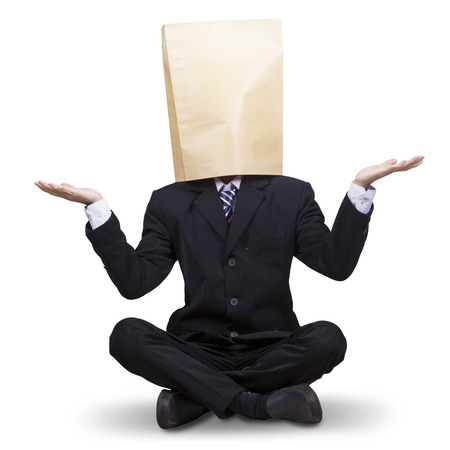ojos vendados: Empresario masculino con los ojos vendados en la cabeza, sentado en el estudio aislado en blanco