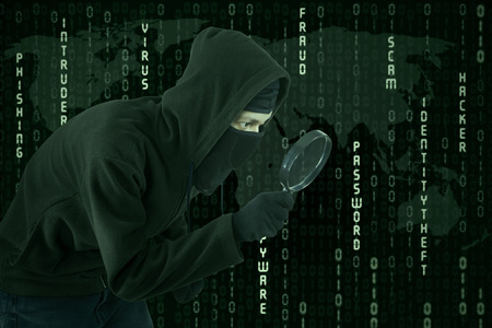 scammer: Male hacker wearing black mask and uses magnifying glass for looking binary code Stock Photo