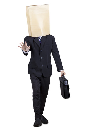 blind person: Male businessman walking with blindfold in the studio, isolated on white background Stock Photo