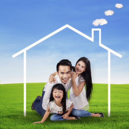 asian home: Portrait of cheerful asian family playing at field under a dream house symbol Stock Photo
