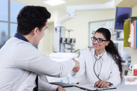 doctor office: Portrait of friendly dentist shaking hands with her patient in the clinic