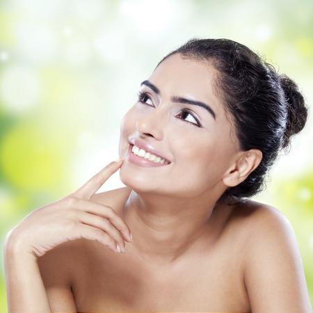 ni�a pensando: Retrato de mujer sonriente con la cara hermosa y una piel suave mirando copyspace contra el fondo bokeh Foto de archivo