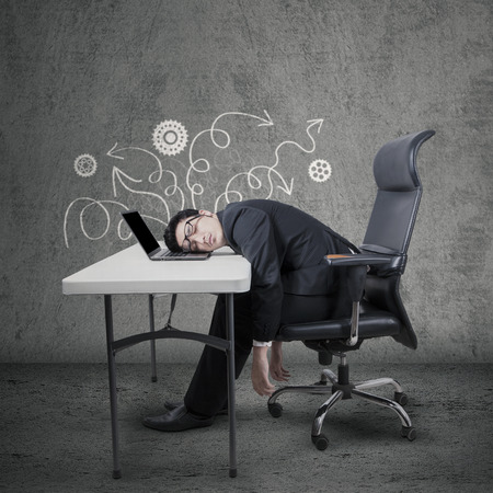Portrait of male entrepreneur in business suit, sitting on chair while sleep on laptop at desk photo