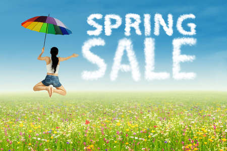 A girl with umbrella jumping beside of spring sale clouds photo