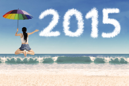 Rear view of woman holding umbrella and leaping frog style on beach celebrate new year photo