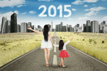Rear view of young mother and daughter walking on the road while holding hands with numbers 2015 on the sky photo