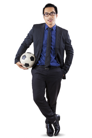 Young asian businessman in business suit, standing in the studio while holding a soccer ball photo